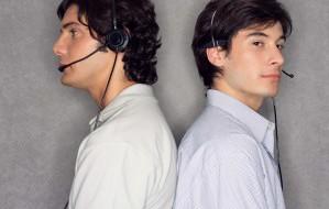 Two men wearing telephone headset